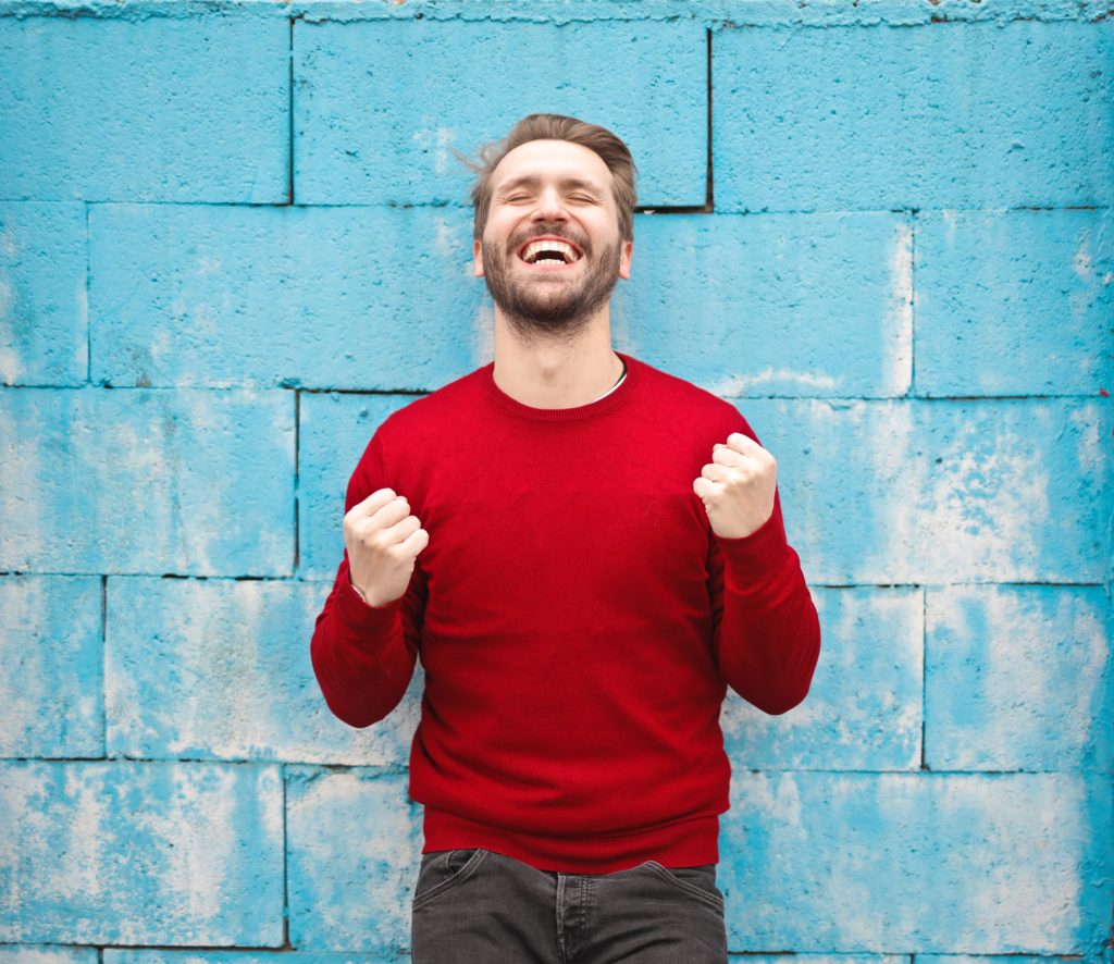 Man Standing in front of Blue Wall
